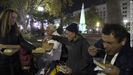 Poor and homeless people eat a lentil stew while a Red Solidaria (Solidarity Network) volunteer offers bread at Plaza de Mayo square, in front of the Casa Rosada government palace in Buenos Aires on April 29, 2016. / AFP / JUAN MABROMATA        (Photo credit should read JUAN MABROMATA/AFP/Getty Images)