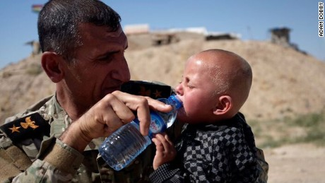 Peshmerga Commander Araz Abdal Rahman gives water to a child at Daqouq.
