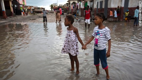 Girls wade through a flooded street in Les Cayes on Thursday, October 6.