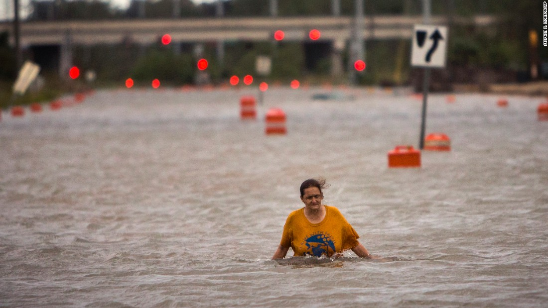A woman who gave her name only as Valerie walks along flooded President Street after leaving her homeless camp in Savannah, Georgia, on October 8.