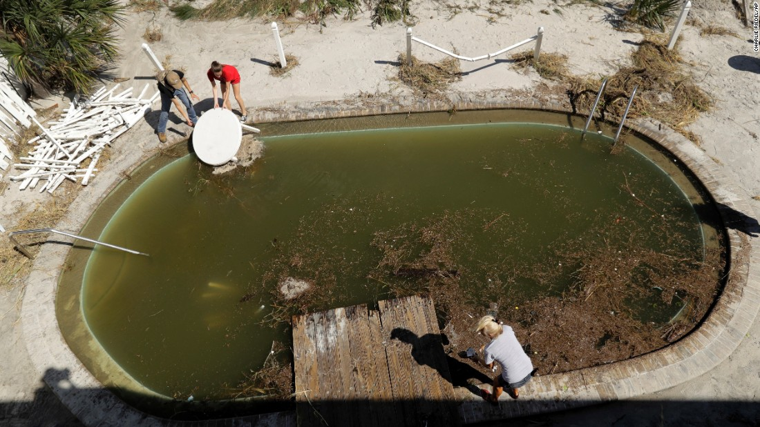 Volunteers clear debris from from a pool at a condominium complex in Jacksonville Beach, Florida, on October 8.