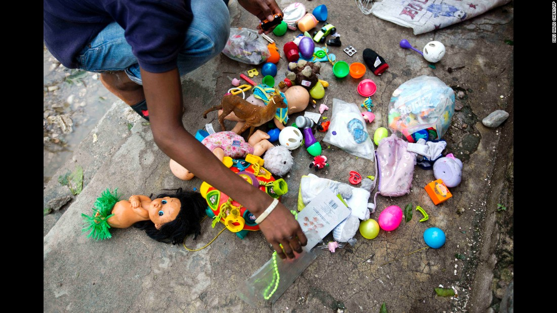 A man dries toys recovered from the debris left by Hurricane Matthew in Les Cayes, Haiti, on Thursday, October 6.
