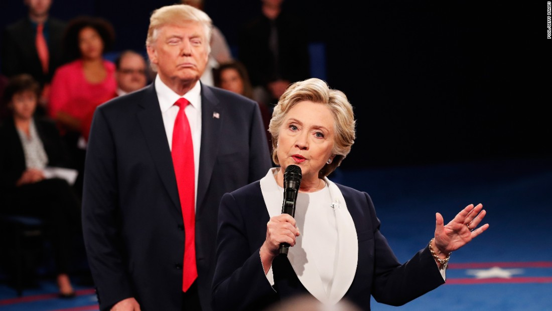 Trump looks on as Clinton answers a question.