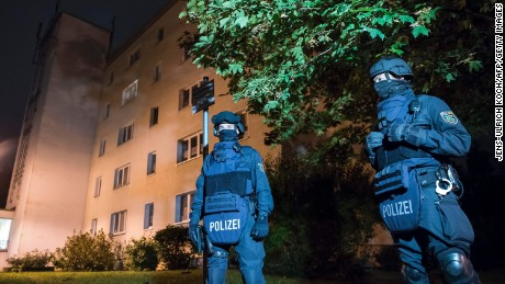 "Policemen in protective cllothing stand in front of at a residential building in Chemnitz, eastern Germany, on October 8, 2016. Police found several hundred grams of ""explosive materials"" in the east German apartment of a Syrian man suspected of planning a bomb attack, and arrested three people connected to him."