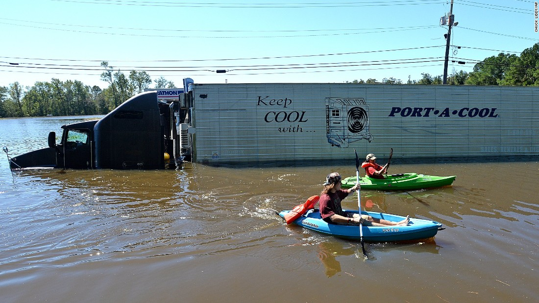 Anthony Writebol, left, and his cousin Melissa Hill paddle past a stranded tractor-trailer in Lumberton on October 9.