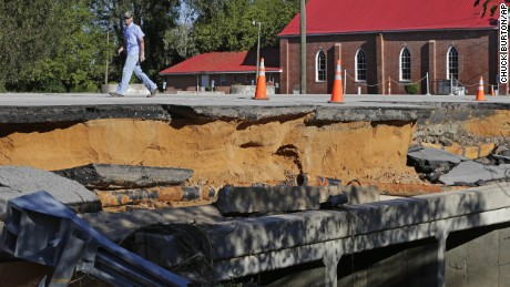 A man walks across a road damaged by flood waters caused by rain from Hurricane Matthew in Fayetteville, N.C., Sunday, Oct. 9, 2016.  Hurricane Matthew's torrential rains triggered severe flooding in North Carolina on Sunday as the deteriorating storm made its exit to the sea, and thousands of people had to be rescued from their homes and cars.