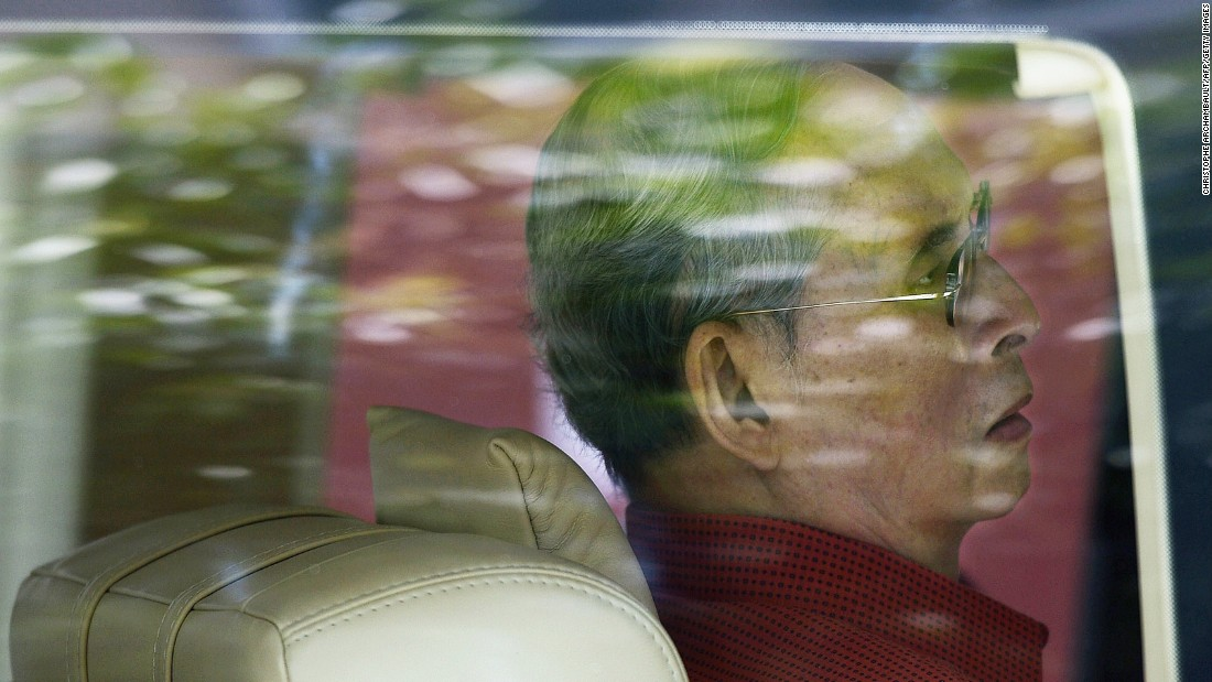 The King is seen through a car window as he leaves the Siriraj hospital in Bangkok in 2015.