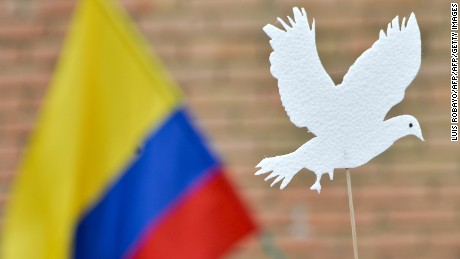A woman holds the figure of a white pidgeon during a march for peace through the streets of Cali, Colombia, on October 9, 2016, just days after voters shot down a historic peace accord between the government and the Revolutionary Armed Forces of Colombia (FARC) to end the war.  Colombia's President Juan Manuel Santos was awarded the Nobel Peace Prize last week for his efforts to end a half-century war with the FARC rebels. / AFP / LUIS ROBAYO        (Photo credit should read LUIS ROBAYO/AFP/Getty Images)