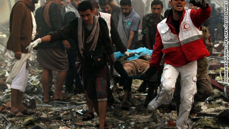 "Yemeni rescue workers carry a victim on a stretcher amid the rubble of a destroyed funeral hall building following reported airstrikes by Saudi-led coalition air-planes on the capital Sanaa on October 8, 2016. Rebels in control of Yemen's capital accused the Saudi-led coalition fighting them of killing or wounding dozens of people in air strikes on Sanaa. The insurgent-controlled news site sabanews.net said that coalition planes hit a building in the capital where people had gathered to mourn the death of an official, resulting in ""dozens of dead or wounded"". / AFP / MOHAMMED HUWAIS        (Photo credit should read MOHAMMED HUWAIS/AFP/Getty Images)"