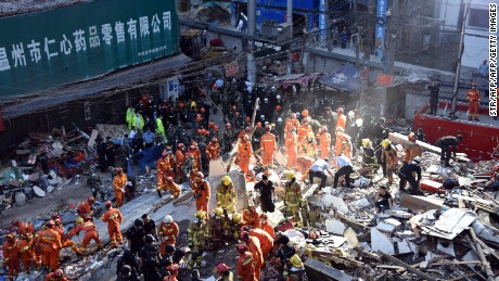 Rescuers search for survivors at an accident site after four buildings caved in during the early hours in Wenzhou, eastern China's Zhejiang province on October 10.