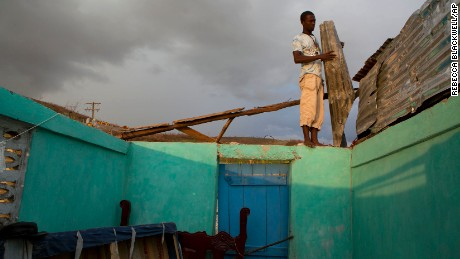 A young man uses salvaged sheets of mangled metal to construct a makeshift roof over one room as a rainstorm rolls in, after his home was damaged by Hurricane Matthew, in Port-a-Piment, Haiti, Monday, Oct. 10, 2016. Nearly a week after the storm smashed into southwestern Haiti, some communities along the southern coast have yet to receive any assistance, leaving residents who have lost their homes and virtually all of their belongings struggling to find shelter and potable water.(AP Photo/Rebecca Blackwell)