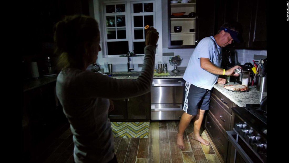 Without power in the hurricane's aftermath, Missy Zinc shines a light so her husband, Shawn, can prepare steaks to grill in Hilton Head, South Carolina, on Sunday, October 9.