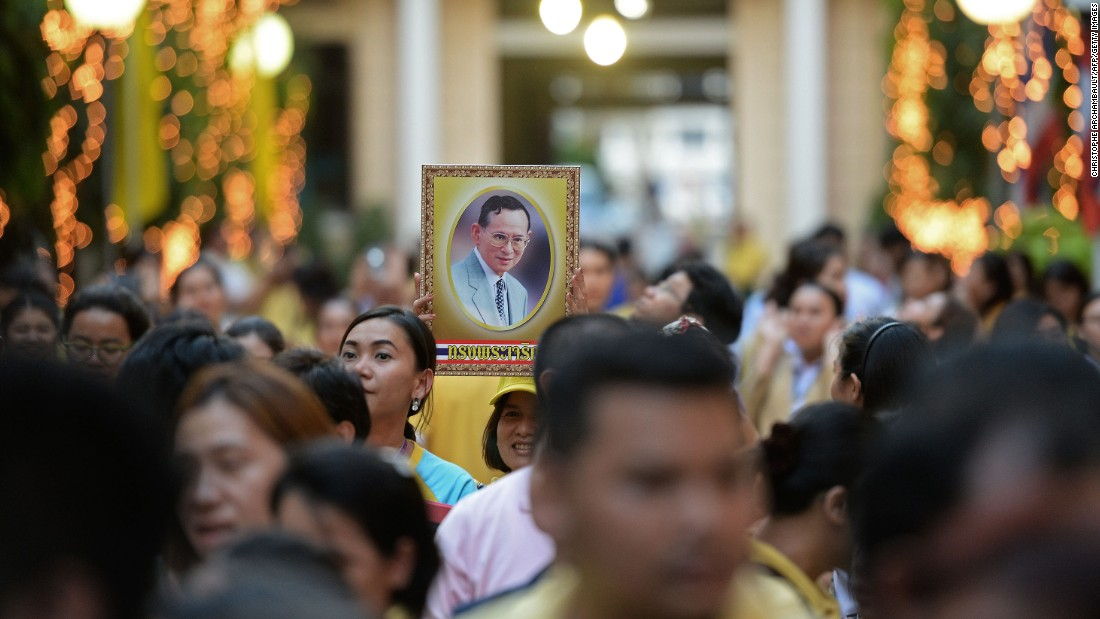 A portrait of the King is held on the eve of his 88th birthday as people gather outside the Siriraj hospital in 2015. The King of Thailand is regarded as a demi-god by many Thais, and his popularity has been viewed as a unifying force during times of political unrest.