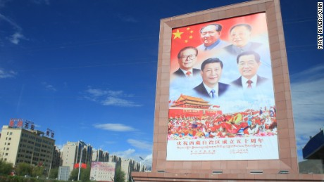 A poster  featuring the headshots of the previous five leaders of China greets visitors outside Lhasa airport.  This same grouping of photos is seen throughout Tibet.