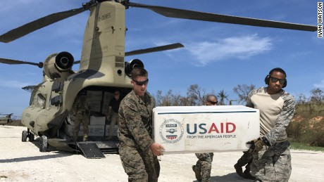 US troops unload plastic tarps for emergency shelters and rice from two US Army Chinooks  outside the hurricane-stricken town of Jeremie.