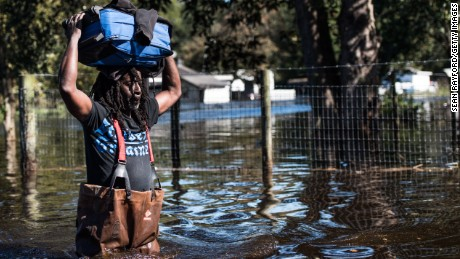 A man carries personal items through a flooded street caused by remnants of Hurricane Matthew on October 11, 2016 in Fair Bluff, North Carolina. Thousands of homes have been damaged in North Carolina as a result of the storm and many are still under threat of flooding.
