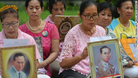 Women hold portraits of Thai King Bhumibol Adulyadej as they pray for his health at Siriraj Hospital in Bangkok on October 12, 2016.