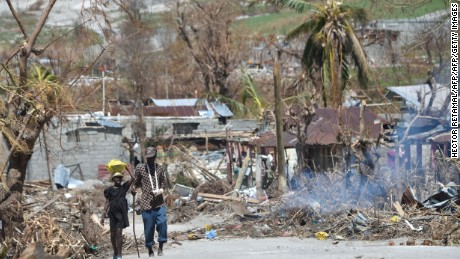 "People walk down a debris covered street in the commune of Port-a-Piment, in Les Cayes, in the southwest of Haiti, on October 11, 2016. Haiti faces a humanitarian crisis that requires a ""massive response"" from the international community, the United Nations chief said Monday, with at least 1.4 million people needing emergency aid following last week's battering by Hurricane Matthew. The storm left at least 372 dead in the impoverished Caribbean nation, with the toll likely to rise sharply as rescue workers reach previously inaccessible areas.   / AFP / HECTOR RETAMAL        (Photo credit should read HECTOR RETAMAL/AFP/Getty Images)"