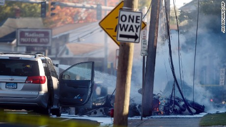 Smoke pours from the smoldering remains of a small plane that crashed on Main Street in East Hartford Connecticut on Tuesday, October 11.