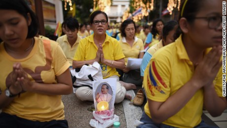 Thais dressed in yellow pray on the ruler's 88th birthday outside a Bangkok hospital in December.
