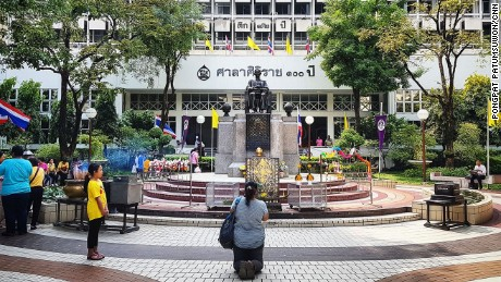 A woman prays for King Bhumibol's speedy recovery outside Siriraj Hospital.