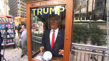 "Meet Trump the Fortune Teller. Jeanne Moos reports animatronic Trump is attracting crowds.    Fortune Teller Trump   The Donald now has a crystal ball and is telling fortunes. The All Seeing Trump is popping up in front of places like Trump Tower and Fox News. And on Wednesday we got a chance to fool around with him as he attracted a crowd of laughing spectators outside the Trump International Hotel. He's an animatronic likeness of the Donald inside a booth. He makes funny predictions about the future (the predictions mock the Donald's positions) and hands out written ""misfortunes."" He's modeled after ""Zoltar"", the fortune teller in the Tom Hanks' movie ""Big."" The All Seeing Trump was the brain child of anonymous Brooklyn artists and is voiced by a comedian impersonating Trump.  Cost to build it...$9000. When they set it up outside Trump Tower, there's video of clueless security looking at it in bewilderment. Finally the police turned off the sound to shut it up. Click link below to hear it."