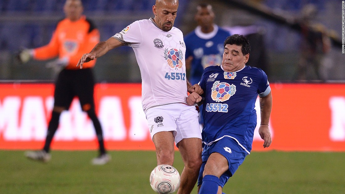 "Diego Maradona clashes with Juan Sebastian Veron (left) during the ""United for Peace"" match in Rome, leading to the former being helped from the pitch enraged at half-time. Pope Francis helped organize the game, which featured footballing greats from around the world."