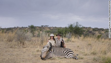 Two young hunters crouch over a dead zebra at the Leopard Lodge, Namibia.