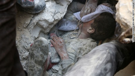TOPSHOT - EDITORS NOTE: Graphic content / Jameel Mustafa Habboush, a 13-year-old Syrian boy receives oxygen as he is pulled from the rubble of a building following Russian air strikes on the rebel-held Fardous neighbourhood of the northern embattled Syrian city of Aleppo on October 11, 2016.   Regime ally Russia carried out its heaviest strikes in days on Syria's Aleppo, causing massive damage in several residential areas of the city's rebel-held east / AFP / THAER MOHAMMED        (Photo credit should read THAER MOHAMMED/AFP/Getty Images)