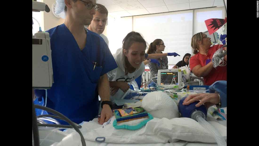 After 27 hours of surgery, Mom and Dad were reunited with both their sons in the pediatric intensive care unit. Nicole McDonald leans over Anias, with Jadon's bed in the background.