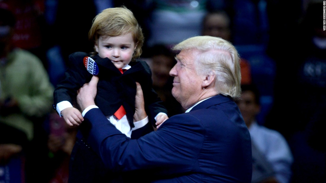 Republican presidential nominee Donald Trump carries a 2-year-old boy named Hunter Tirpak, who was dressed like Trump, at a rally in Wilkes-Barre, Pennsylvania, on Monday, October 10.