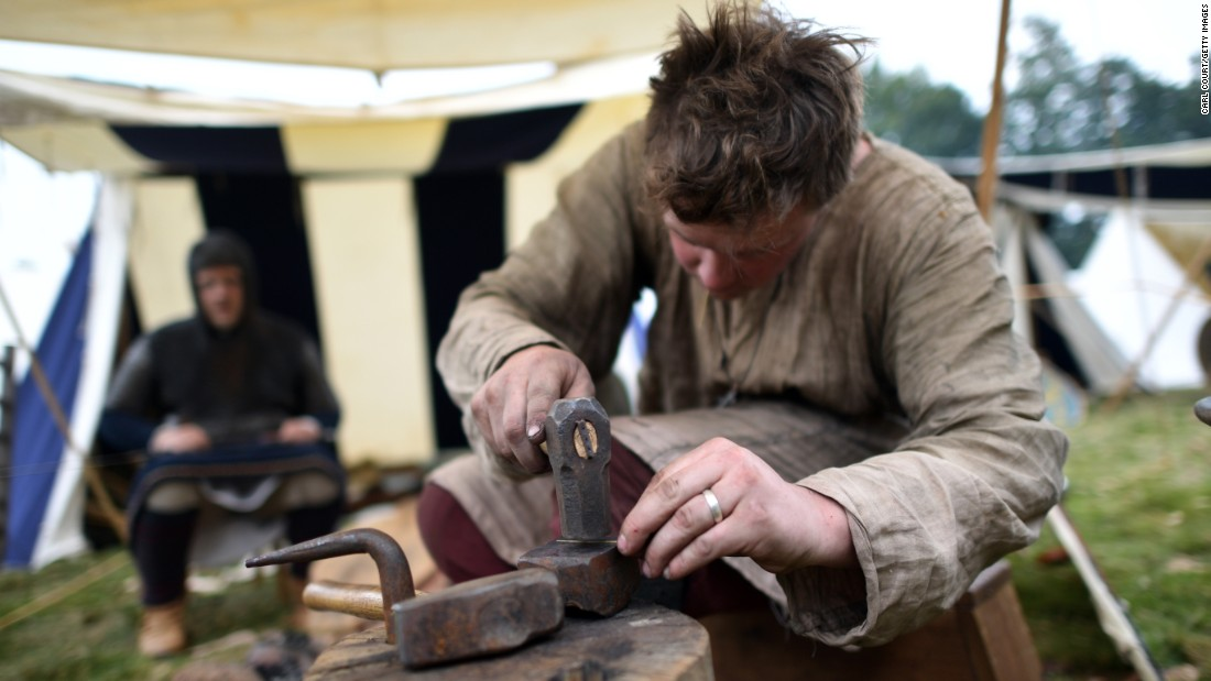 A re-enactor playing a blacksmith hammers a small piece of metal.