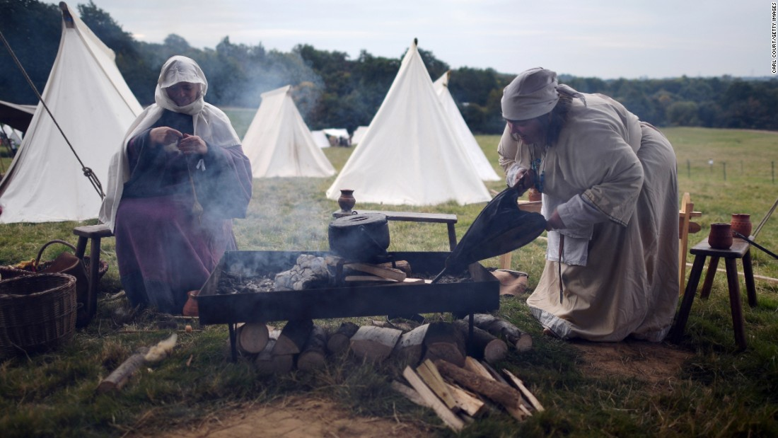 A re-enactor uses a bellows to start a camp fire.