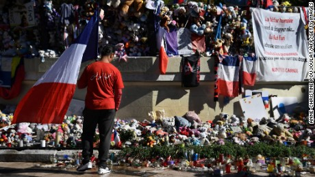 A man wearing a shirt reading in Arabic 'Long live Tunisia' and carrying the French national flag looks at candles, toys and flowers placed in commemoration to victims in front of a pavilion at the Promenade des Anglais in Nice, southeastern France, on October 15, 2016, on the occasion of a national tribute to the victims of the July 14 terror attack in which a truck ploughed into crowds celebrating Bastille Day, killing 86 people and injuring more than 400.