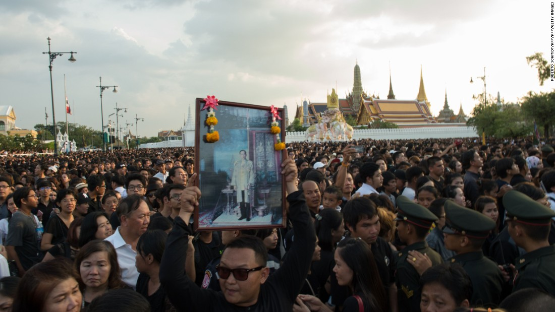 A Thai man carries high an image of Thailand's King Bhumibol Adulyadej as a large crowd floods the streets leading to the Royal Palace on October 14, 2016.