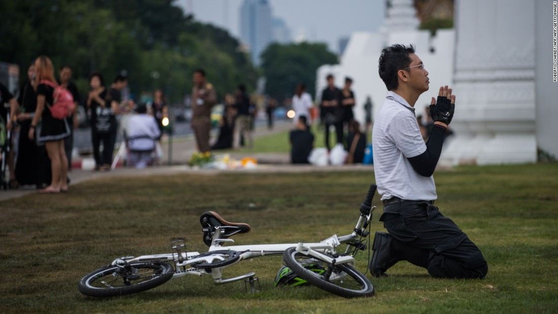 A Thai cyclist prays in front of the Grand Palace in Bangkok on October 16, 2016. Thousands of Thai men and women gather daily in the vicinity of the palace to pray for the late Thai King Bhumibol Adulyadej after his death Thursday.