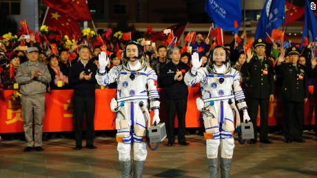 Chinese astronauts Jing Haipeng, right, and Chen Dong, left, wave farewell to the crowd before getting on Shenzhou 11 on Oct. 17, 2016.