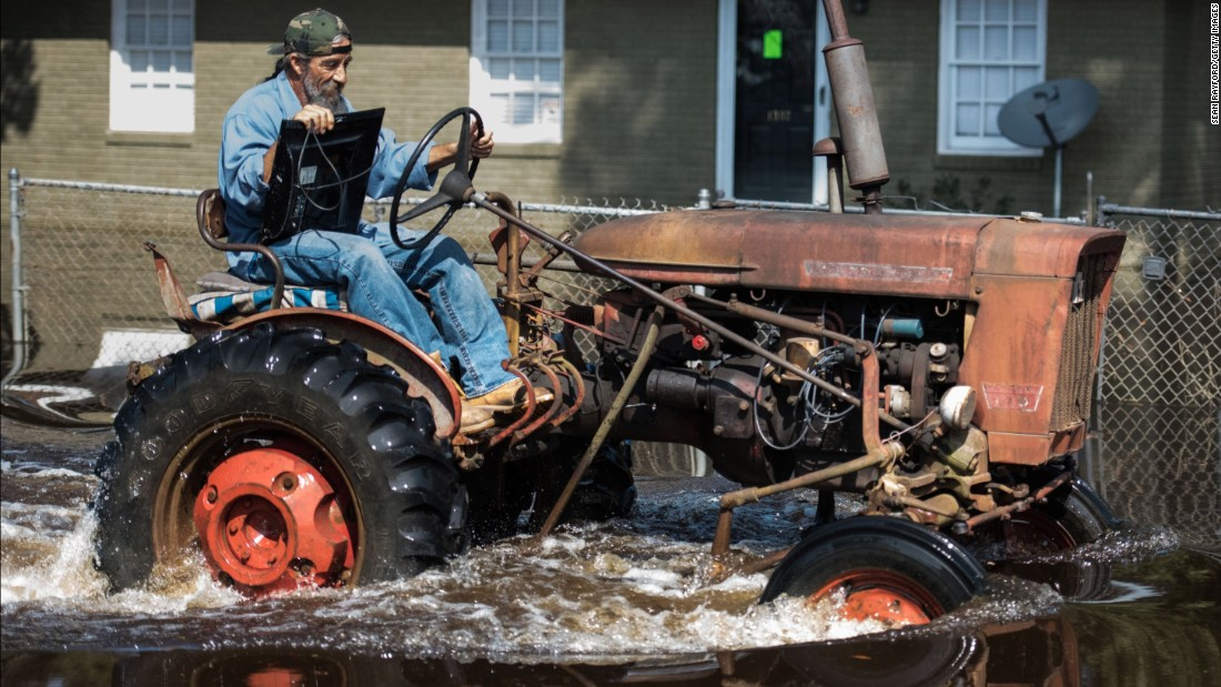 Riding a tractor, a man retrieves a television from his North Carolina home on Saturday.