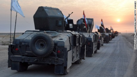 Pro-government forces drive military vehicles toward the city of Mosul.