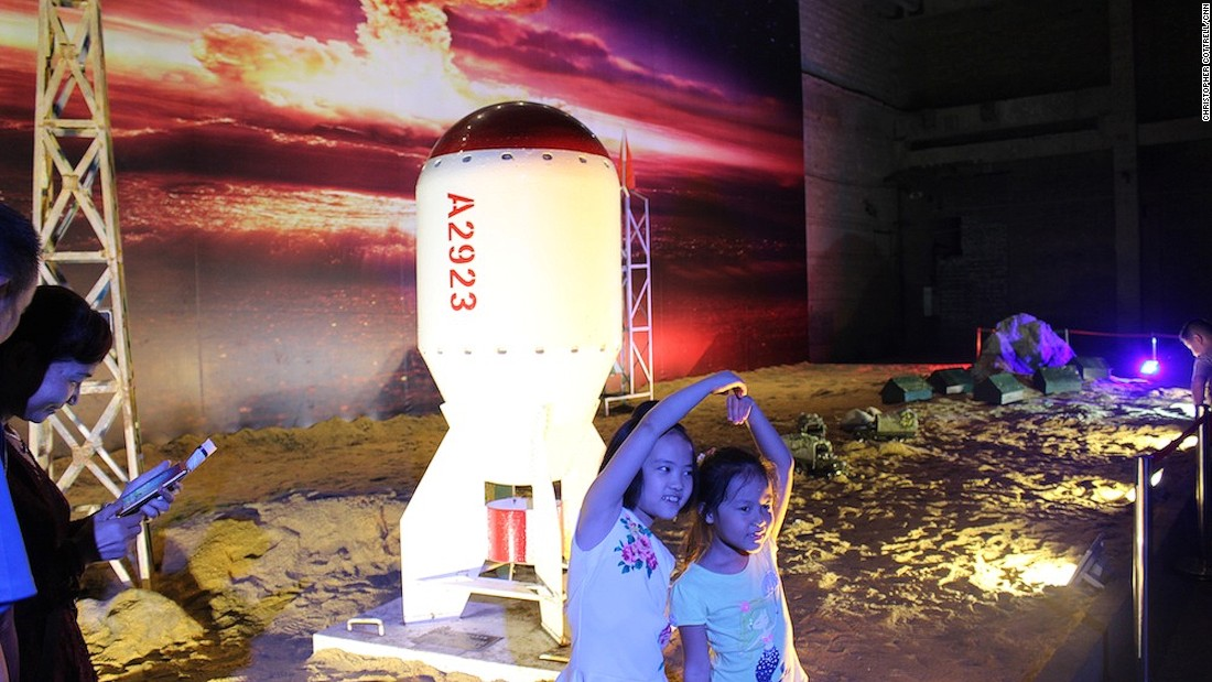 Children pose in front of a life-size replica of China's first atomic bomb, which was detonated during a nuclear test in 1964.