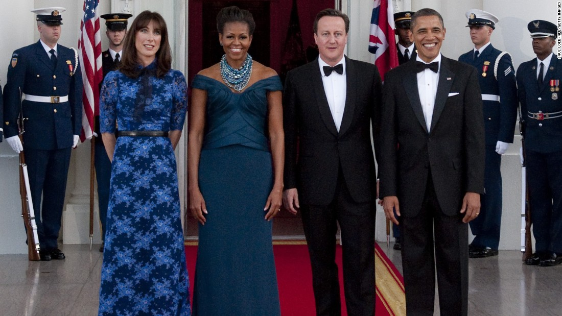 President Barack Obama and first lady Michelle Obama stand alongside British Prime Minister David Cameron and wife Samantha Cameron as they arrive for a state dinner at the White House on March 14, 2012.