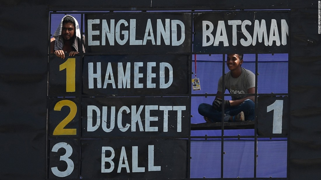 Scoreboard operators watch the English cricket team play the Bangladesh Cricket Board XI in Chittagong, Bangladesh, on Saturday, October 15.