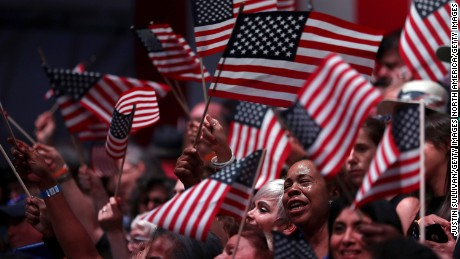 Supporters of democratic presidential candidate former Secretary of State Hillary Clinton wave American flags during a primary night event on June 7, 2016 in Brooklyn, New York. Six states will vote in presidential primaries a day after the Associated Press declared that Hillary Clinton has enough delegates to become the presumptive democratic nominee.