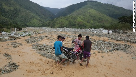 Residents carry a motorbike along a destroyed highway following heavy rains brought by Typhoon Sarika in the town of Gabaldon, Nueva Ecija province, north of Manila on October 16.