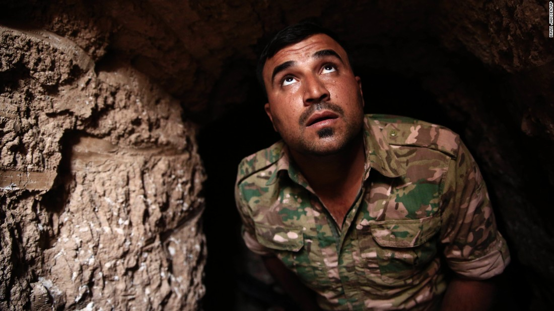 A Peshmerga fighter peers up from an underground tunnel in the liberated town of Badana on October 18. ISIS fighters have built tunnels below residential streets to escape from airstrikes.