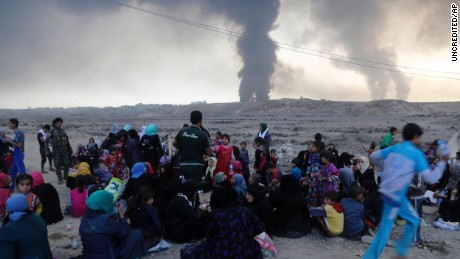 Smoke rises as people flee their homes during clashes between Iraqi security forces and ISIS near Mosul, Iraq.