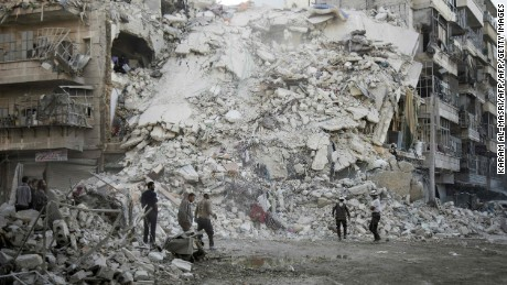 Members of the Syrian Civil Defence, known as the White Helmets, search for victims amid the rubble of a destroyed building following reported air strikes in the rebel-held Qatarji neighbourhood of the northern city of Aleppo, on October 17, 2016. KARAM AL-MASRIKARAM AL-MASRI/AFP/Getty Images