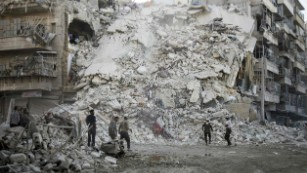 Rescue workers search for victims amid the rubble of a destroyed building following air strikes in Aleppo on October 17, 2016.
