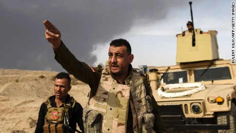 "TOPSHOT - CORRECTION - A member of Iraqi forces gestures as troops head to the frontline on October 18, 2016 near the town of Qayyarah, south of Mosul, during the operation to recapture the city from the Islamic State group. Tens of thousands of Iraqi forces were making gains on the Islamic State group in Mosul in an offensive US President Barack Obama warned would be a ""difficult fight"". A massive cloud of dark grey smoke blots out the horizon as the result of oil wells being set afire by IS in an effort to provide cover from air strikes. / AFP PHOTO / BULENT KILIC / The erroneous mention[s] appearing in the metadata of this photo by BULENT KILIC has been modified in AFP systems in the following manner: [date is October 18] instead of [October 16]. Please immediately remove the erroneous mention[s] from all your online services and delete it (them) from your servers. If you have been authorized by AFP to distribute it (them) to third parties, please ensure that the same actions are carried out by them. Failure to promptly comply with these instructions will entail liability on your part for any continued or post notification usage. Therefore we thank you very much for all your attention and prompt action. We are sorry for the inconvenience this notification may cause and remain at your disposal for any further information you may require.BULENT KILIC/AFP/Getty Images"