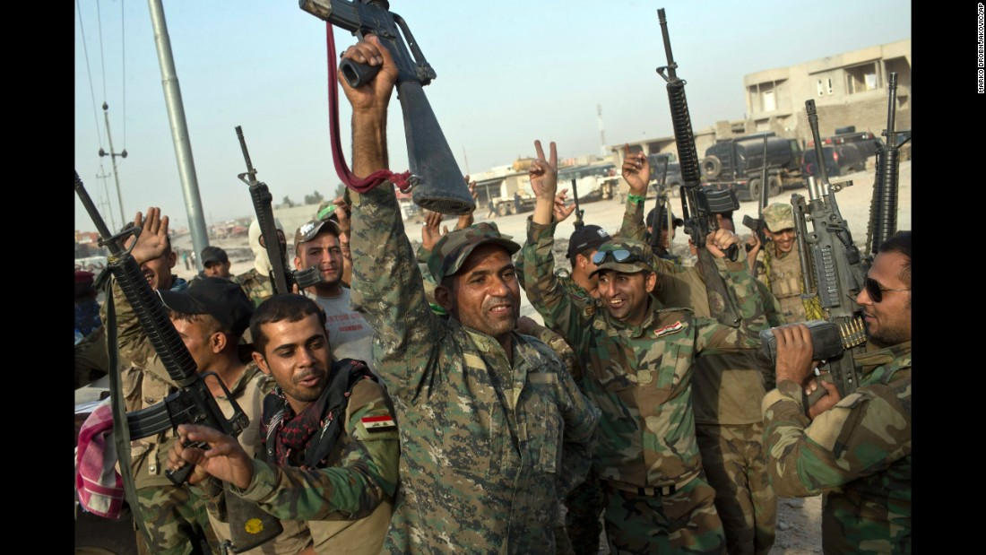Iraqi soldiers raise their weapons in celebration on the outskirts of Qayyara on October 19.